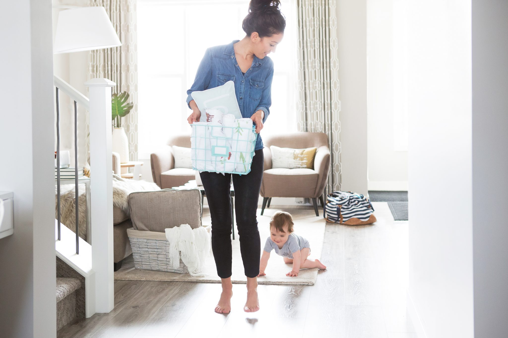 Stay at home mom doing laundry with crawling baby in tow. Many moms find that it's cheaper to be a stay at home mom, and it isn't just ditching daycare that saves you money.